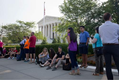People wait in line to enter the Supreme Court in Washington, Thursday June 25, 2015. The court is expected to hand down decisions today. Two major opinions, health care and gay marriage, are among the remaining to be released before the term ends at the end of June. (AP Photo/Jacquelyn Martin)