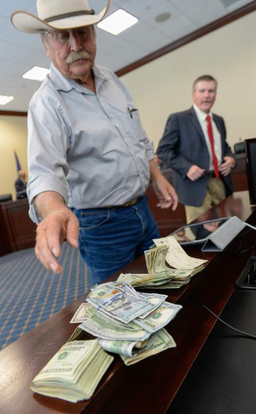 Francisco Kjolseth | The Salt Lake Tribune Garfield County Commissioner Dell LeFevre drops money on the table in support of San Juan County Commissioner Phil Lyman's defense. Members of Utah's Constitutional Defense Council met at the Capitol on Wednesday, June 24, 2015, to hear Kanab Republican Rep. Mike Noel make a case for setting aside money for Phil Lyman's legal bills. In the end it was decided that money will be raised by private donations.
