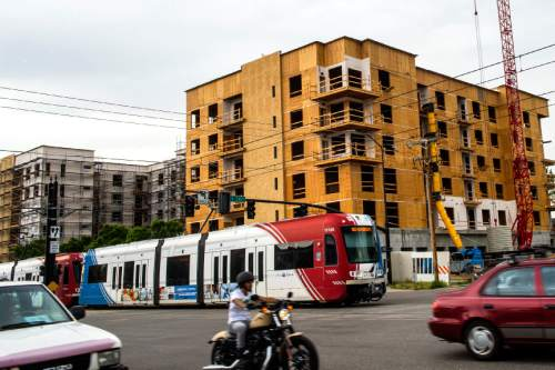 Chris Detrick  |  Tribune file photo TRAX train zips past apartment construction along 400 South and 500 East. A new study says one of the big benefits of mass transit is development and jobs.