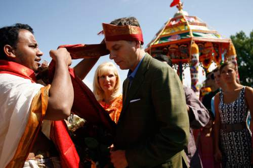Chris Detrick |  Tribune file photo Priest Satish Kumar of the Sri Ganesha Hindu Temple of Utah welcomes Gov. Gov. Jon Huntsman Jr. with a traditional silken turban while First Lady Mary Kaye Huntsman looks on in 2008.