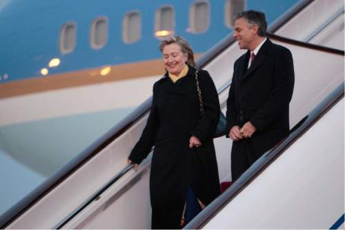 US Secretary of State Hillary Rodham Clinton, left, and US Ambassador to China Jon Huntsman, right, walk down the steps of Air Force One during the arrival of President Barack Obama at Capital International Airport in Beijing, China, Monday, Nov. 16, 2009. (AP Photo/Pablo Martinez Monsivais)