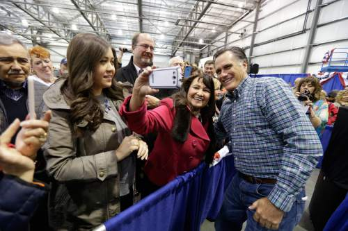 "Former Republican presidential nominee Mitt Romney, right, poses for a ""selfie"" photo with a supporter as he appears at a campaign rally for Republican U.S. Senate candidate Dan Sullivan, Monday, Nov. 3, 2014, in Anchorage Alaska. Sullivan is challenging U.S. Sen. Mark Begich, D-Alaska. (AP Photo/Ted S. Warren)"