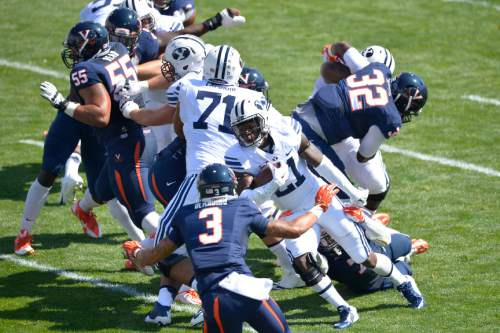 Chris Detrick  |  The Salt Lake Tribune Brigham Young Cougars running back Jamaal Williams (21) runs past Virginia Cavaliers safety Quin Blanding (3) during the game at LaVell Edwards Stadium Saturday September 20, 2014.  Virginia is winning the game 16-13 at halftime.