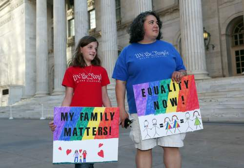 Nine-year-old Lillian Gutierrez, left, joins her mother, Veronica, both of Denver, in waving placards at a protest outside the Federal Courthouse in downtown Denver on Wednesday, April 9, 2014. The protest, sponsored by Support Marriage Equality in Colorado, was held as a federal appeals court weighs inside the Denver courthouse whether to give an important victory to gay couples' right to marry in Utah and Oklahoma. (AP Photo/David Zalubowski)