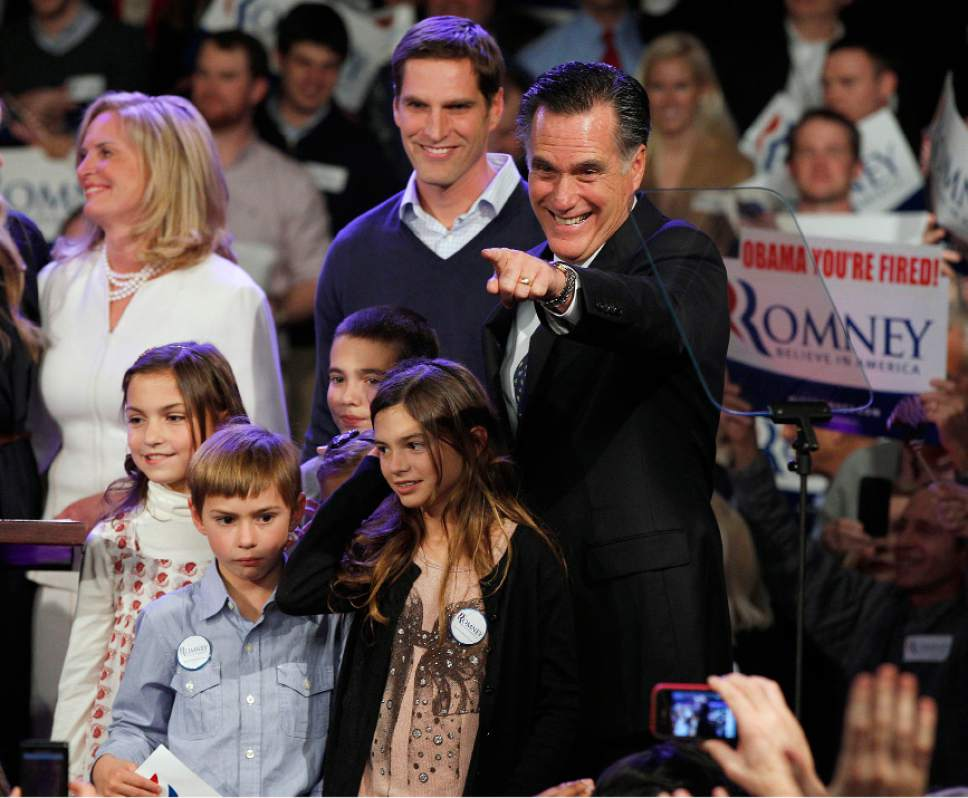 Former Massachusetts Gov. Mitt Romney surrounded by his family points towards supporters at the Romney for President New Hampshire primary night victory party at Southern New Hampshire University in Manchester, N.H., Tuesday, Jan. 10, 2012. (AP Photo/Elise Amendola)