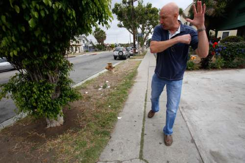 "In this Thursday, June 4, 2015 photo, David Klinger reenacts the moments before he shot a man attacking his police partner in south-central Los Angeles on the sidewalk where it happened. Edward Randolph, who he thought was an innocent bystander at a crime scene, pulled out a butcher knife and attacked his partner, Dennis Azevedo. ""Shoot him,"" Azevedo cried, as he fought from the ground, holding Randolph's hands to try to keep the blade from striking his neck. Rushing from across the street, Klinger grabbed Randolph's left wrist, but Randolph broke free. ""I blamed myself for 20 years for not being able to wrest the knife from him,"" Klinger says now. When he got hold of his own gun and then pulled the trigger, ""it was a soft pop, and I thought, 'That was odd,'"" Klinger says, recalling how he watched the bullet hit Randolph in the chest from two feet away. (AP Photo/Martha Irvine)"