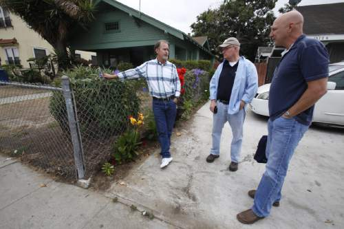 "In this Thursday, June 4, 2015 photo, David Klinger, right, stands with his former training officer, Robie McIntosh, left and his former supervising officer, Tim Anderson, in the south-central Los Angeles neighborhood where they all once worked together. Anderson says, it's rare for a rookies to face the situation Klinger did so early in his career. ""This was the ultimate test for him"" _ and he passed, Anderson says. (AP Photo/Martha Irvine)"