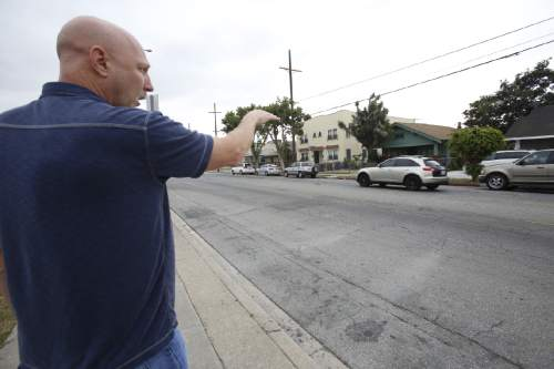 "In this Thursday, June 4, 2015 photo, David Klinger points across a street in south-central Los Angeles to the spot where he, as a rookie police officer, shot a man attacking his partner. On July 25, 1981, Klinger and Dennis Azevedo were called to a home where an armed burglar had been reported. ""Get out of here! Get out of here!"" the officers yelled to those gathering to watch. Most spectators left, except 26-year-old Edward Randolph. Because of the helicopter noise, Azevedo says he didn't think Randolph could hear him, or maybe he didn't speak English. So he ran across the street to try to get him to move. Instead, Randolph pulled a butcher knife from a bag over his shoulder and attacked Azevedo. (AP Photo/Martha Irvine)"