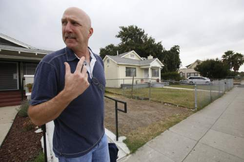 "In this Thursday, June 4, 2015 photo, David Klinger stands in a neighborhood in south-central Los Angeles where he used to work as a police officer. Examining police shootings under an academic lens, he has learned from other officers about a sense of time slowing down or tunnel vision, or even shifting to oddly mundane thoughts when a shooting happens. And he analyzes his own experience differently, realizing now that that the soft ""pop"" he thought he heard when he pulled the trigger was that type of perceptual distortion. (AP Photo/Martha Irvine)"