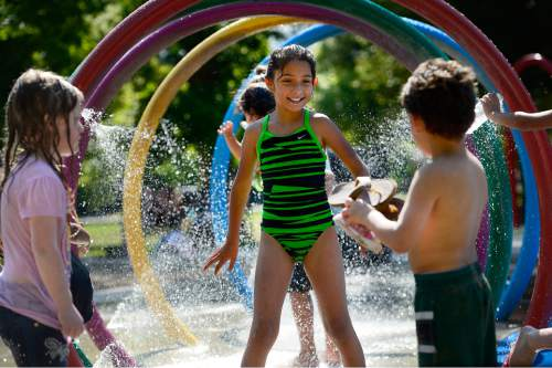 Scott Sommerdorf   |  The Salt Lake Tribune Kids play at the splash pad water play area inside Liberty Park's Rotary Playground, Monday, June 29, 2015.