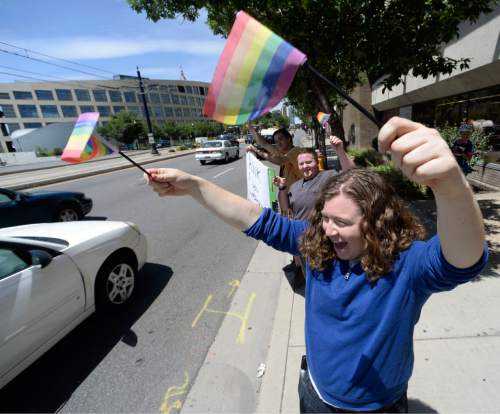 Al Hartmann  |  The Salt Lake Tribune  Cappy Shapiro waves rainbow flag in a honk and wave in front of the Utah Pride Center in Salt Lake City Tuesday June 25 celebrating the 10th Circuit Courts ruling that states outlawing same-sex marriage are in violation of the U.S Constitution.