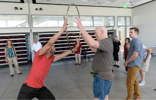 Francisco Kjolseth | The Salt Lake Tribune   In a collaboration between the Department of Physical Therapy and the Department of Modern Dance, Assistant Professor Juan Carlos Claudio, left, passes a hoop to Dan Gwin as they express themselves through creative movement during a class to help those living with Parkinson's Disease like Dan. Research has shown that dancing helps Parkinson's patients with motor skills.