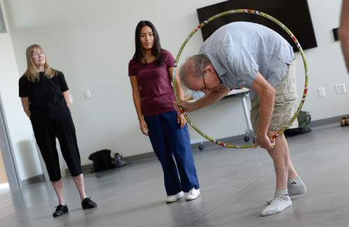 Francisco Kjolseth | The Salt Lake Tribune   Wes Starkenburg who has been affected by Parkinson's Disease, uses a hoop to express himself through creative movement before passing it on to the next person. In a collaboration between the Department of Physical Therapy and the Department of Modern Dance at the University of Utah, people living with the disease work to maintain their motor skills through dance, creative movement, and physical therapy.