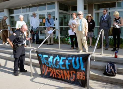 Al Hartmann |  The Salt Lake Tribune A small group from Peaceful Uprising, Utah Tar Sands Resistance and concerned citizens read statements and performed a skit with children on the steps of the Utah Department of Natural Resources as a security guard records them before a crucial hearing Tuesday, June 30 at the Utah Division of Oil, Gas and Mining in Salt Lake City.