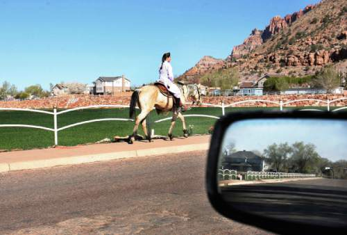 Scott Sommerdorf   The Salt Lake Tribune A woman rides a horse up Center Street in Colorado City toward the Canaan Mountains on a quiet day in 2008.