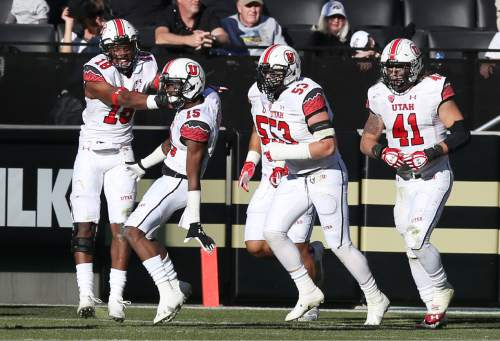 From left, Utah defensive back Eric Rowe celebrates with defensive back Dominique Hatfield after Hatfield returned an interception for touchdown as linebackers Jason Whittingham and Jared Norris look on in the fourth quarter of Utah's 38-34 victory over Colorado in an NCAA college football game in Boulder, Colo., on Saturday, Nov. 29, 2014. (AP Photo/David Zalubowski)