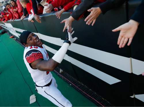 Utah defensive back Dominique Hatfield is congratulated by fans as he leaves the field Utah's 38-34 victory over Colorado in an NCAA college football game in Boulder, Colo., Saturday, Nov. 29, 2014. Hatfield intercepted a pass and scored the winning touchdown in the fourth quarter to secure the win for Utah. (AP Photo/David Zalubowski)