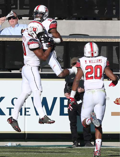 Utah defensive back Dominique Hatfield, center, with linebacker Pita Taumoepenu, left,  after returning an interception for a touchdown during the fourth quarter of an NCAA college football game against Colorado in Boulder, Colo., on Saturday, Nov. 29, 2014. (AP Photo/David Zalubowski)