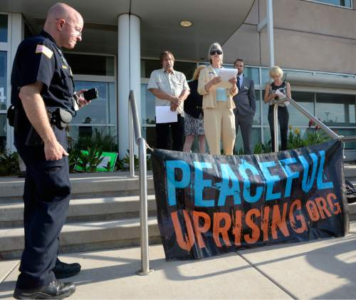 Al Hartmann |  The Salt Lake Tribune A small group from Peaceful Uprising, Utah Tar Sands Resistance and concerned citizens read statements and performed a skit with children on the steps of the Utah Dept. of Natural Resources as a security guard records them before a crucial hearing Tuesday, June 30 at the Utah Division of Oil, Gas and Mining in Salt Lake City.