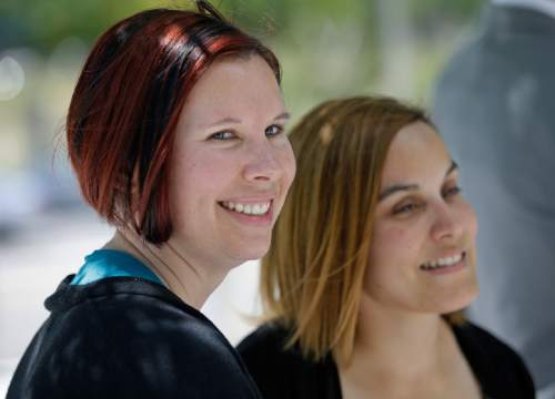 Angie, right, and Kami Roe of West Jordan, leave the federal courthouse Wednesday, July 15, 2015, in Salt Lake City. A federal judge has ordered the state of Utah to list the names of the lesbian couple on a birth certificate as the mothers of their new baby. U.S. District Judge Dee Benson said Wednesday the case wasn't hard to decide in the wake of the U.S. Supreme Court ruling legalizing same-sex marriage. (AP Photo/Rick Bowmer)