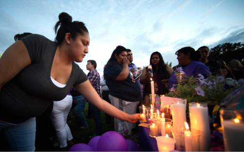 Rick Egan  |  The Salt Lake Tribune  Mercedes Charley lays a candle in remembrance of Kailey Vijil, as friends and family gathered for a candle light vigil, in memory of the 12-year-old West Valley City girl who died earlier this week, Sunday, July 19, 2015.