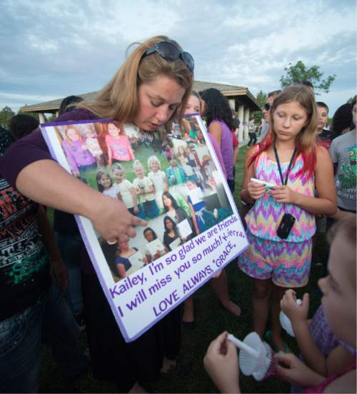 Rick Egan  |  The Salt Lake Tribune  Mamie Kynaston shows a collage of pictures of Kailey from grade school, as friends and family of Kailey Vijil gather for a candle light vigil, in memory of the 12-year-old West Valley City girl who died earlier this week, Sunday, July 19, 2015.