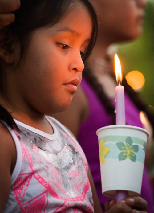Rick Egan  |  The Salt Lake Tribune  Bobbi Smith,7, holds a candle, as friends and family of Kailey Vijil gathered for a candle light vigil, in memory of the 12-year-old West Valley City girl who died earlier this week, Sunday, July 19, 2015.