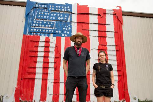 Jeremy Harmon  |  The Salt Lake Tribune  IATSE (International Alliance of Theatrical Stage Employees) members Josh and Heidi Belka stand outside the IATSE union building in Salt Lake City on Wednesday, July 22, 2015. Behind them is their mural of labor icon Joe Hill that was painted over with a US flag. The mural was painted over by other members of the union who objected to the murals political tone.