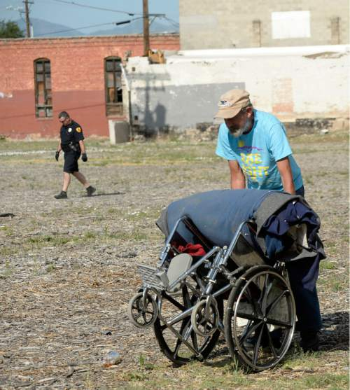Al Hartmann     Tribune file photo Homeless man with belongings on his wheelchair makes his way across lot posted no tresspassing at 500 W. and 350 S. as a Salt Lake Policeman patrols the area.
