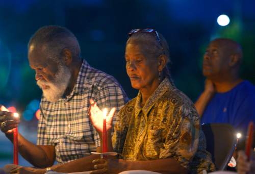 Leah Hogsten     The Salt Lake Tribune Robert and Lucinda Sampson, longtime members of Trinity AME Church shield their candles from the breeze during a vigil on Friday. Trinity AME Church held a half hour vigil to honor the nine victims of the Charleston, SC shooting and an hour-long discussion afterwards. The SLC congregation is one of several AME churches across the nation in taking part in the vigil.