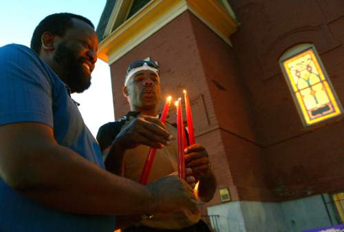 Leah Hogsten     The Salt Lake Tribune l-r Lee Johnson and Kevin Nelson light candles for visitors to the vigil. Trinity AME Church held a half hour vigil to honor the nine victims of the Charleston, SC shooting and an hour-long discussion afterwards. The SLC congregation is one of several AME churches across the nation in taking part in the vigil, July 24, 2015.