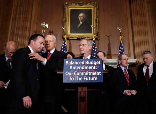 Senate Republican leader Mitch McConnell of Kentucky gathers other Republican senators to call for an amendment to the Constitution requiring a balanced federal budget, at the Capitol in Washington, Thursday, March 31, 2011. To the left are Sen. Orrin Hatch, R-Utah, conferring with freshman Sen. Mike Lee, R-Utah. (AP Photo/J. Scott Applewhite)