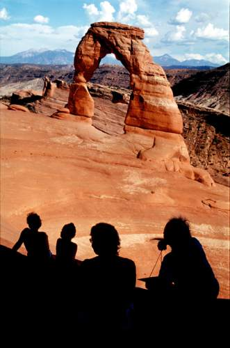 Tourists sit quietly as they view Delicate Arch in Arches National Park in this 2000 AP file photo.