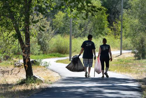 Scott Sommerdorf   |  The Salt Lake Tribune Volunteers walk along the Jordan River Parkway as they help during the cleanup of the Jordan River. United by Blue hosted a cleanup of the Jordan River in advance of the Outdoor Retailer summer market. The organization pledges to remove one pound of trash from oceans and waterways for every product sold. Volunteers collected 531 pounds of trash.