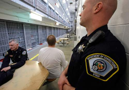 Department of Corrections Officers are shown with an inmate in Wasatch A-East block during a media tour Thursday, Feb. 26, 2015, at the Utah State Correctional Facility in Draper, Utah. Gov. Gary Herbert said Thursday that he's opposed to the idea of allowing a state commission to pick a location to build a new prison instead of leaving the decision with the Legislature. (AP Photo/Rick Bowmer, Pool)