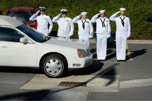 Scott Sommerdorf   |  The Salt Lake Tribune A Navy honor guard salutes as a hearse carrying the remains of 22 veterans whose remains have never been claimed. They were interred in a service at the state veterans cemetery in Bluffdale, Saturday, August 1, 2015. Also present were honor guards from the Army and Air Force.
