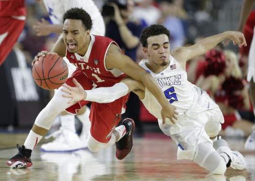 Duke's Tyus Jones (5) and Utah's Brandon Taylor vie for a loose ball during the second half of a college basketball regional semifinal game in the NCAA Tournament Friday, March 27, 2015, in Houston. (AP Photo/Charlie Riedel)
