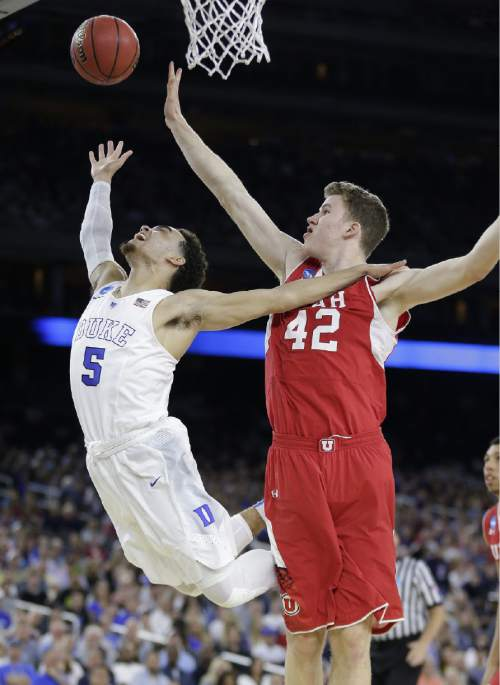 Utah's Jakob Poeltl (42) knocks the ball away from Duke's Tyus Jones (5) during the second half of a college basketball regional semifinal game in the NCAA Tournament Friday, March 27, 2015, in Houston. (AP Photo/Charlie Riedel)