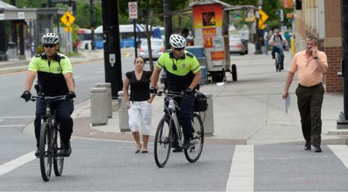 Francisco Kjolseth  |  The Salt Lake Tribune Salt Lake City police officers Bryce Curdie, left, and Slade Bailey patrol the streets near The Gateway on Wednesday, June 10, 2015. The City Council will spend more money on bicycle cops in the first part of the coming fiscal year. The council has budgeted $1.1 million for eight bike patrol officers and eight social workers. The mayor's proposed $254 million budget starts July 1. The new bike patrols are expected in September.