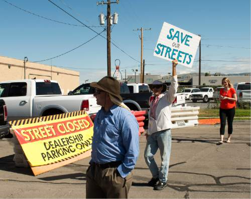 Rick Egan  |  The Salt Lake Tribune  Timothy Dvorsky holds a sign in protest along with other South Salt Lake residents. They marched to State Street to demonstrate their opposition to the noise, inconvenience and increased traffic caused by the closure of Burton and Truman Avenues, Saturday, Aug. 8, 2015.