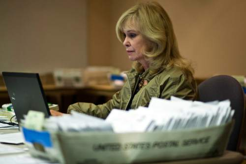 Chris Detrick  |  Tribune file photo Salt Lake County Clerk Sherrie Swensen verifies some of the thousands of provisional and mail-in ballots during a previous election cycle. Fourteen of 16 Salt Lake County cities are using vote-by-mail this year.