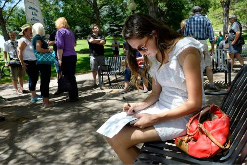 Scott Sommerdorf   |  The Salt Lake Tribune Stephanie Engle fills out her resignation letter during a rally and mass resignation from the LDS Church, Saturday, July 25, 2015. Later about 200 people marched to the church office buliding and back to City Creek Park.