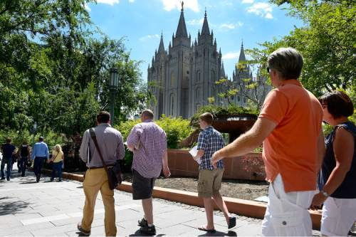 Scott Sommerdorf   |  The Salt Lake Tribune About 200 people marched past the LDS Salt Lake temple after crossing North Temple Street on their way to the church office building to deliver their resignation letters, Saturday, July 25, 2015.