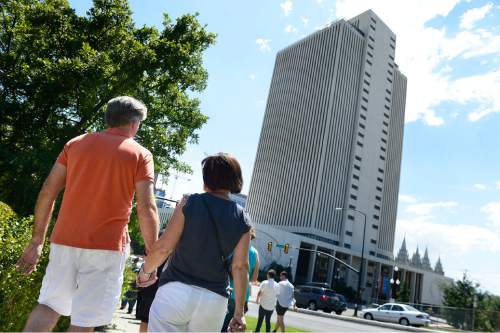 Scott Sommerdorf   |  The Salt Lake Tribune A couple holding hands were part of a group of about 200 people marching from City Creek Park on their way to the church office building to deliver their resignation letters, Saturday, July 25, 2015.
