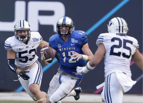 Memphis quarterback Paxton Lynch (12) looks for an open teammate as he is rushed by Brigham Young linebacker Sione Takitaki (53) and linebacker Teu Kautai (25) during the second half of the in the inaugural Miami Beach Bowl football game, Monday, Dec. 22, 2014 in Miami. Memphis defeated Brigham Young 55-48 in double overtime. (AP Photo/Wilfredo Lee)