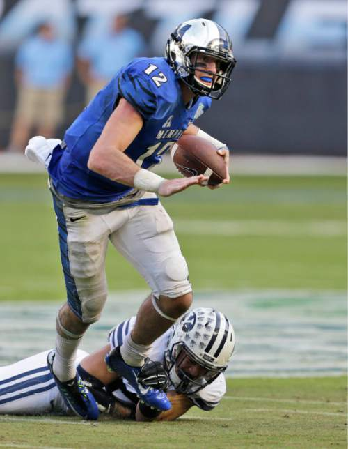 Memphis quarterback Paxton Lynch (12) is tackled by Brigham Young linebacker Sione Takitaki (53) during the second half of the in the inaugural Miami Beach Bowl football game, Monday, Dec. 22, 2014 in Miami. Memphis defeated Brigham Young 55-48 in double overtime. (AP Photo/Wilfredo Lee)