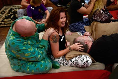 "Scott Sommerdorf   |  The Salt Lake Tribune Tim Longwell, left, Jenny Evans, and Steve Afrin, right during a ""cuddle party"" - a regular meet-up that happens in Utah, where strangers get together and cuddle in a nonsexual way, Friday, July, 31, 2015."