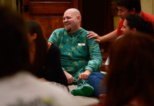 "Scott Sommerdorf   |  The Salt Lake Tribune Tim Longwell laughs as he describes his St. Patrick's Day-themed onesie during a ""cuddle party"" - a regular meet-up that happens in Utah, where strangers get together and cuddle in a nonsexual way, Friday, July, 31, 2015. Doug Roberts is at right."