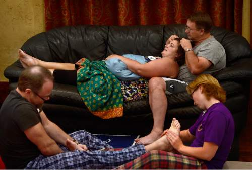 "Scott Sommerdorf   |  The Salt Lake Tribune Joe Tuttle, left foreground, and Amber Van Dusen massage each other's feet, while Scott Nelsen and Kori Keylon are on the couch during a ""cuddle party"" - a regular meet-up that happens in Utah, where strangers get together and cuddle in a nonsexual way, Friday, July, 31, 2015."