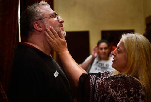"Scott Sommerdorf   |  The Salt Lake Tribune Steve Afrin has his beard stroked by Pam Bradford during a ""cuddle party"" - a regular meet-up that happens in Utah, where strangers get together and cuddle in a nonsexual way, Friday, July, 31, 2015."